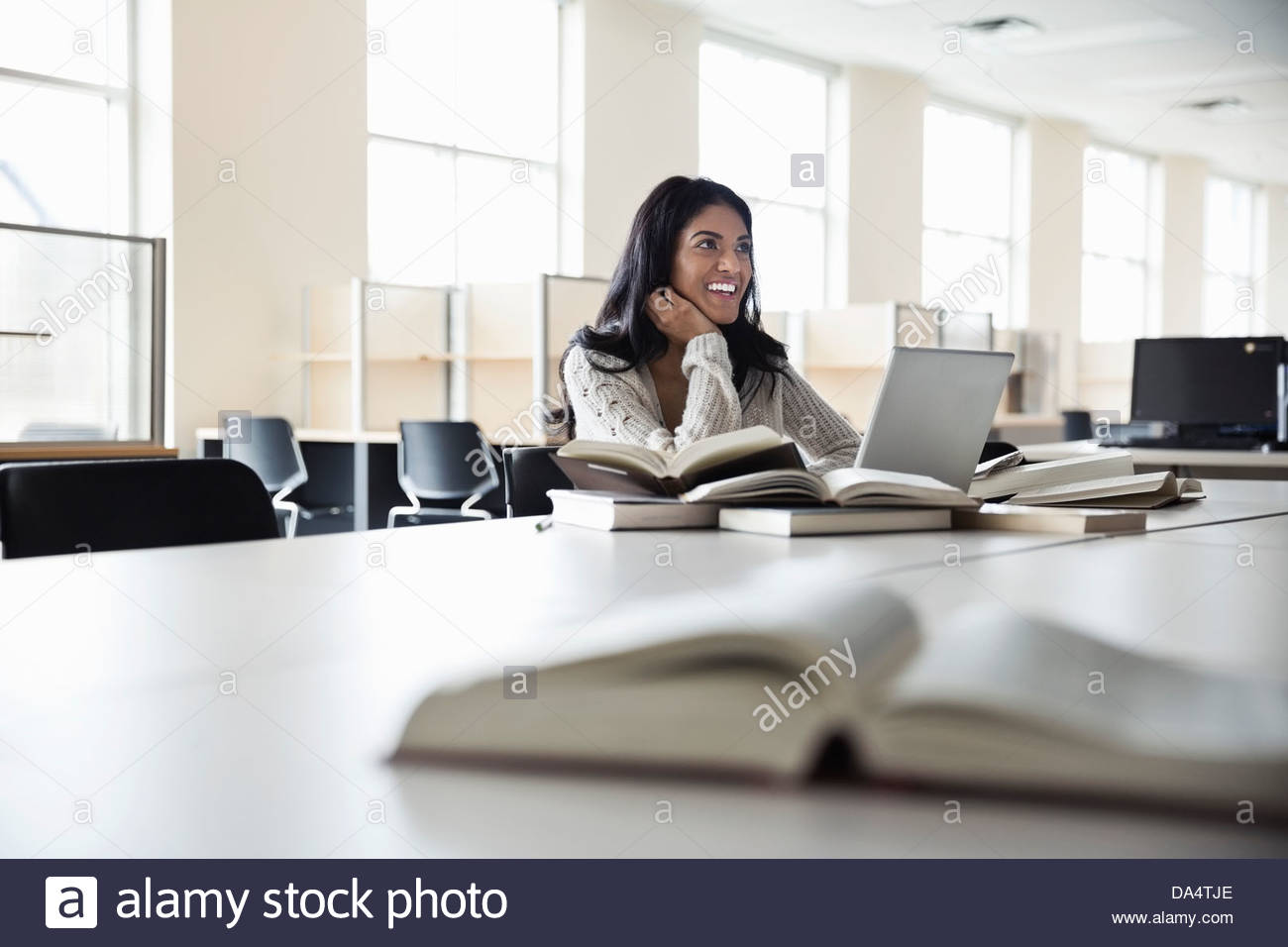 Female student with laptop doing research in college library - Stock Image