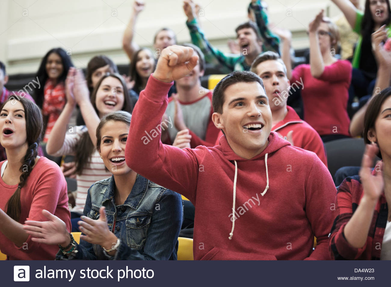 Large group of students cheering at college sporting event - Stock Image