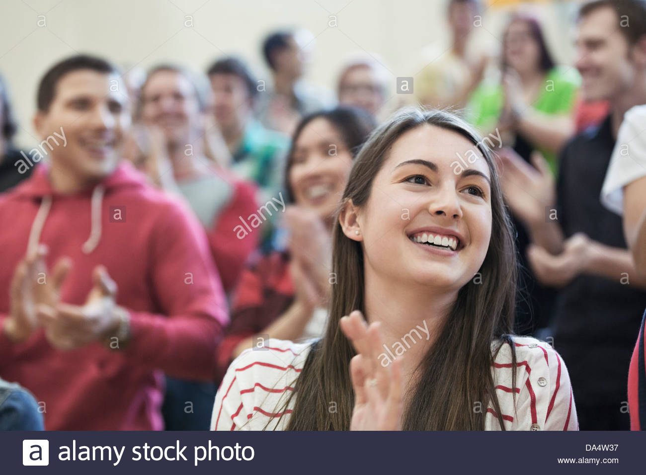 Female student clapping at college sporting event - Stock Image