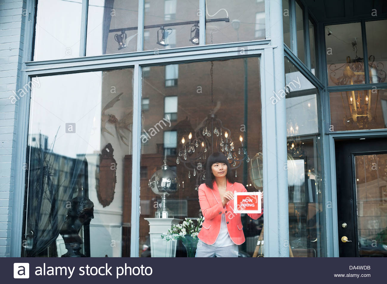 Female business owner displaying help wanted sign in furniture store window - Stock Image