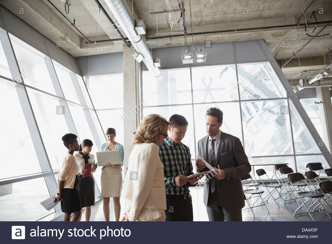 Group of business people with technology talking in office building - Stock Image