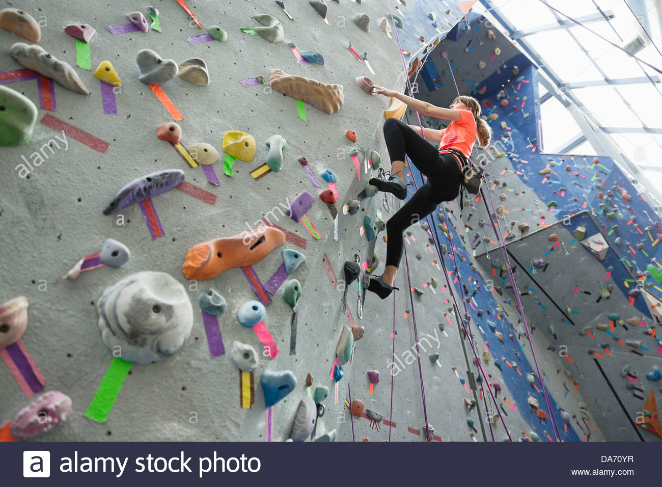 Low angle view of woman climbing on climbing wall at gym - Stock Image