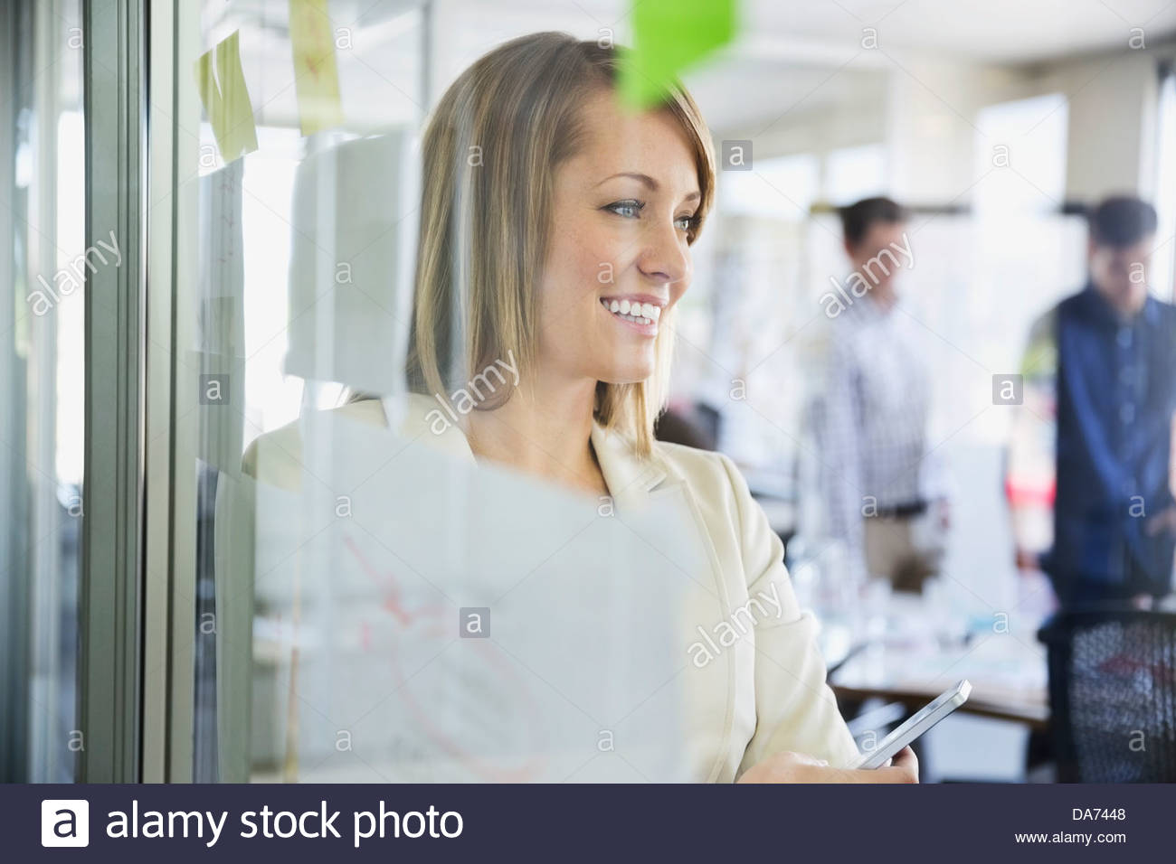 Businesswoman standing by glass wall in office - Stock Image