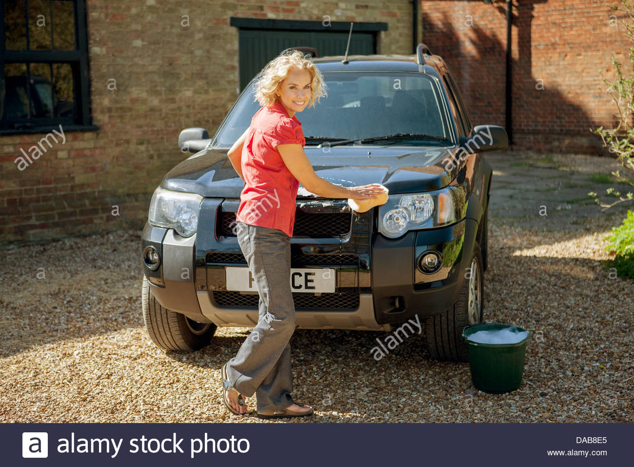 A mature woman washing a four wheel drive car - Stock Image