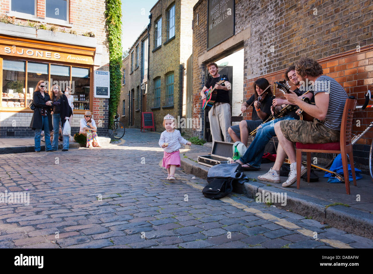 A band of young buskers perform on the streets of London at Columbia Road flower market, London, England, GB, UK. Stock Photo