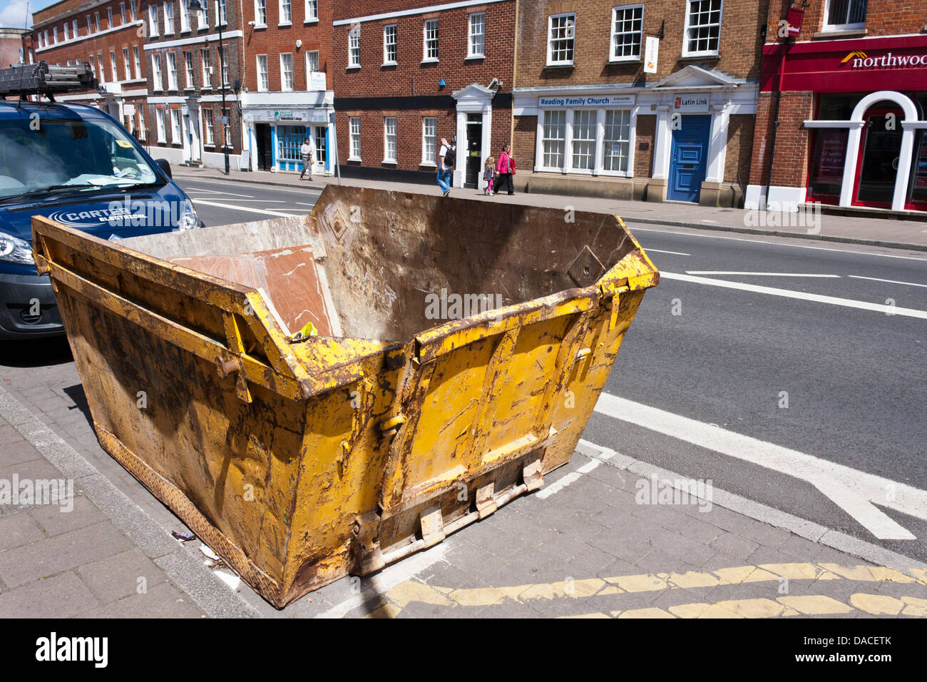 Builders skip on street ready to be filled with waste. Reading, Berkshire, England, GB, UK Stock Photo