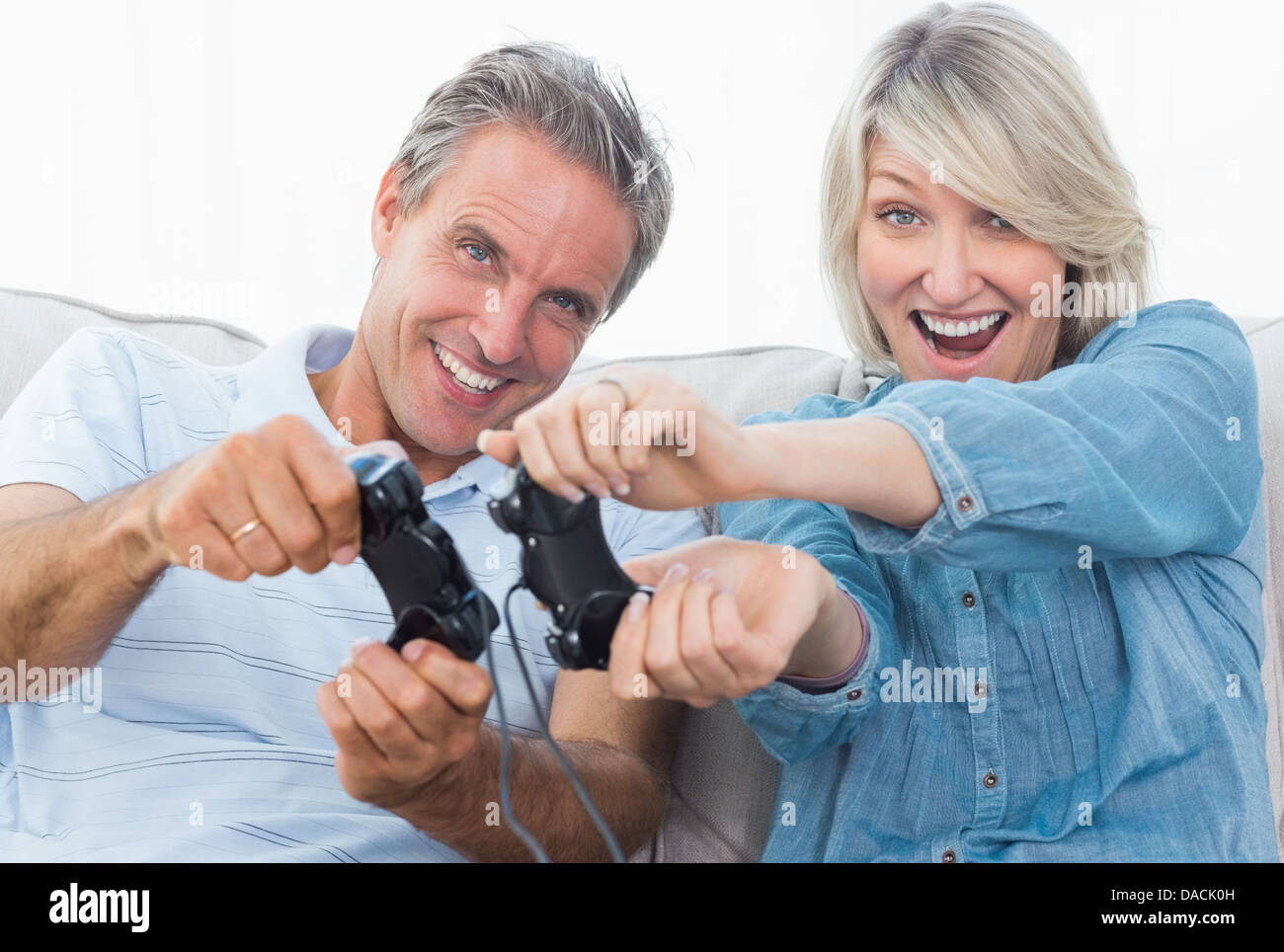 Couple playing video games on the couch - Stock Image