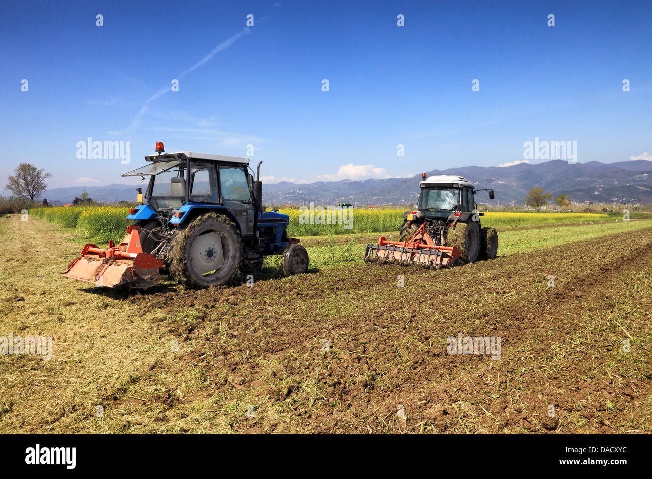 agriculture concept, tractors plowing a field - Stock Image