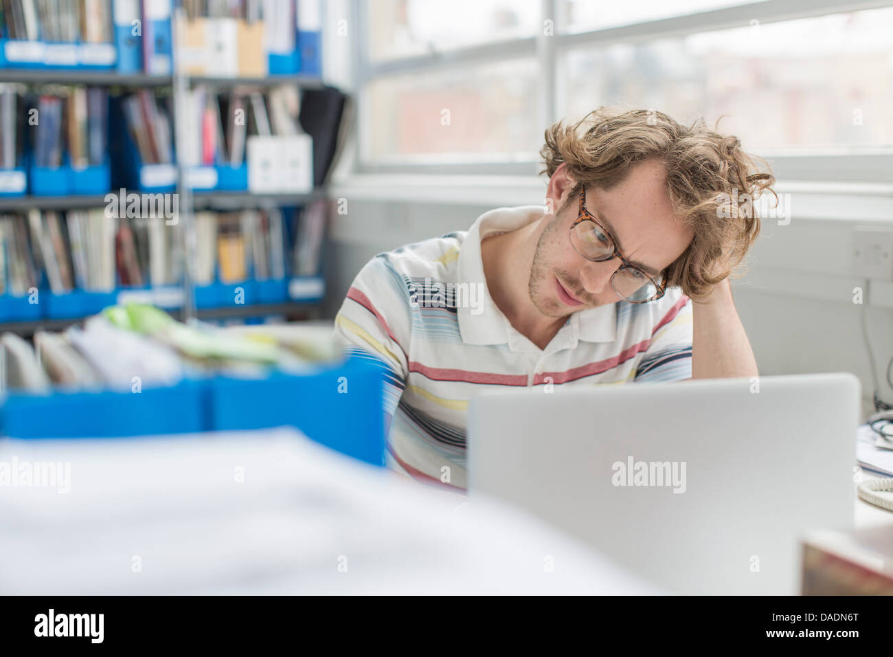 Young man with head in hands in creative office - Stock Image