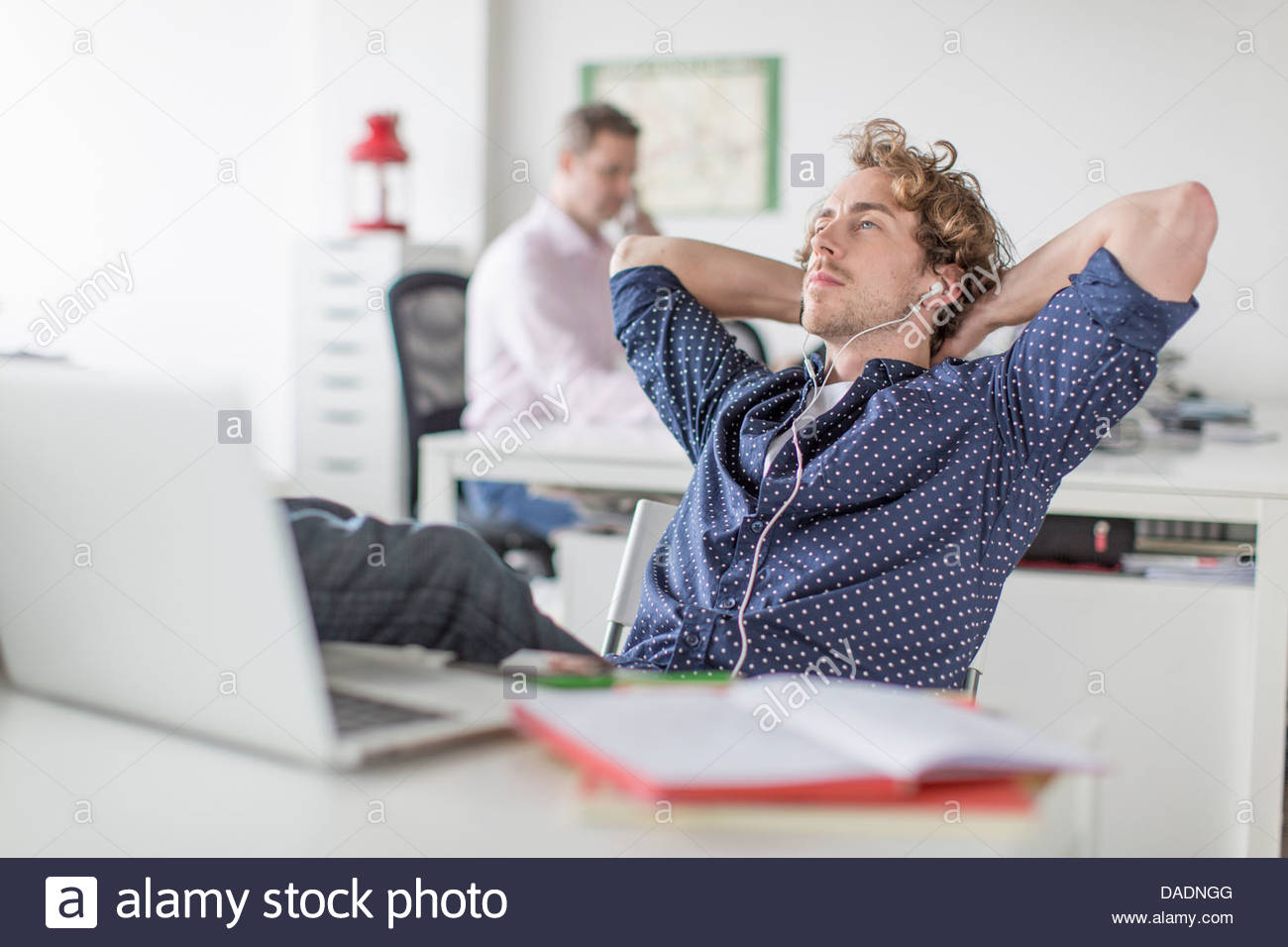 Young office worker reclining at desk with hands behind head - Stock Image