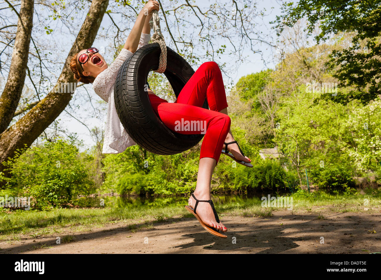 Young woman having fun on tire swing - Stock Image