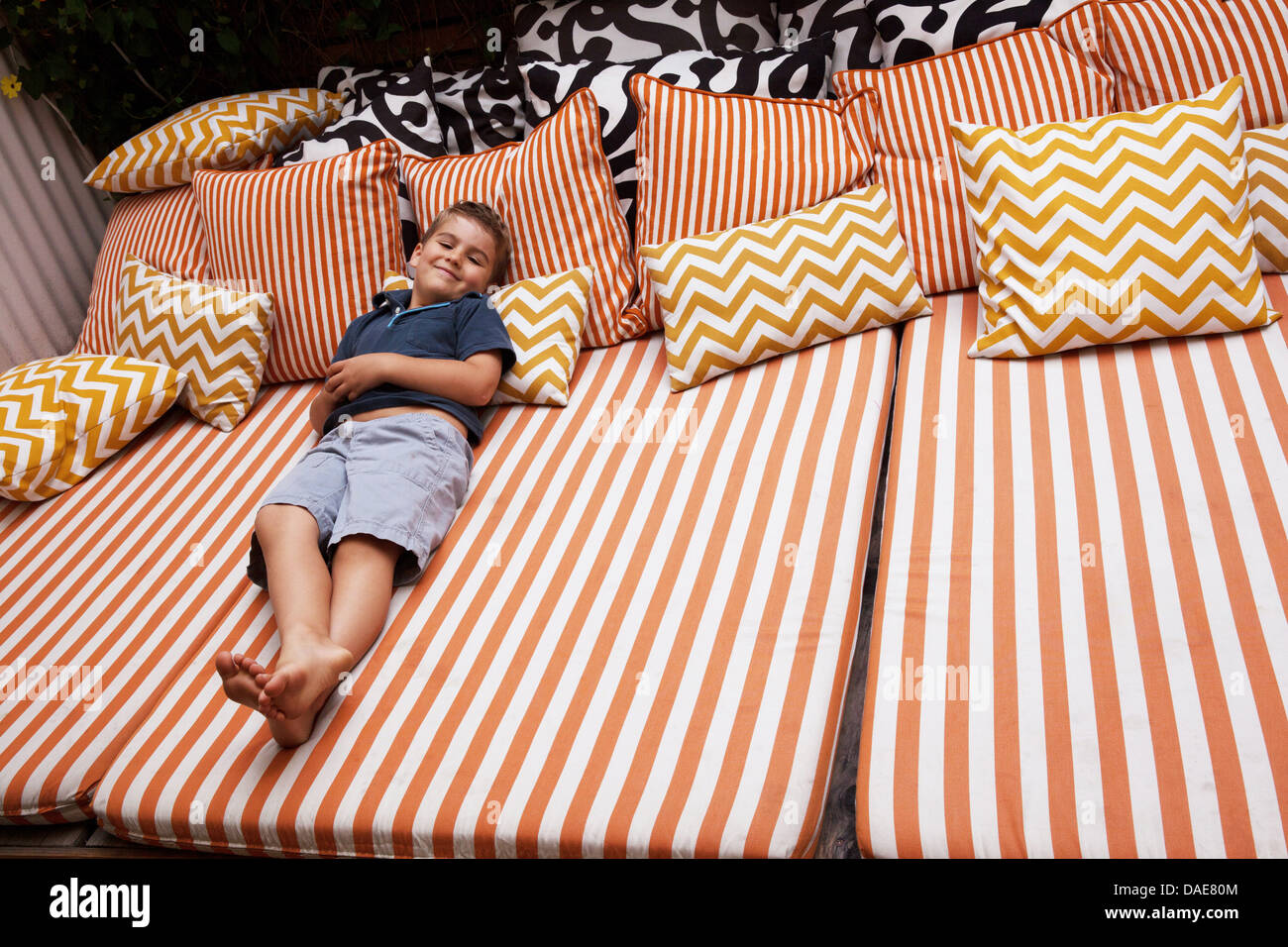 Boy Relaxing On Striped Outdoor Furniture With Cushions Stock Photo