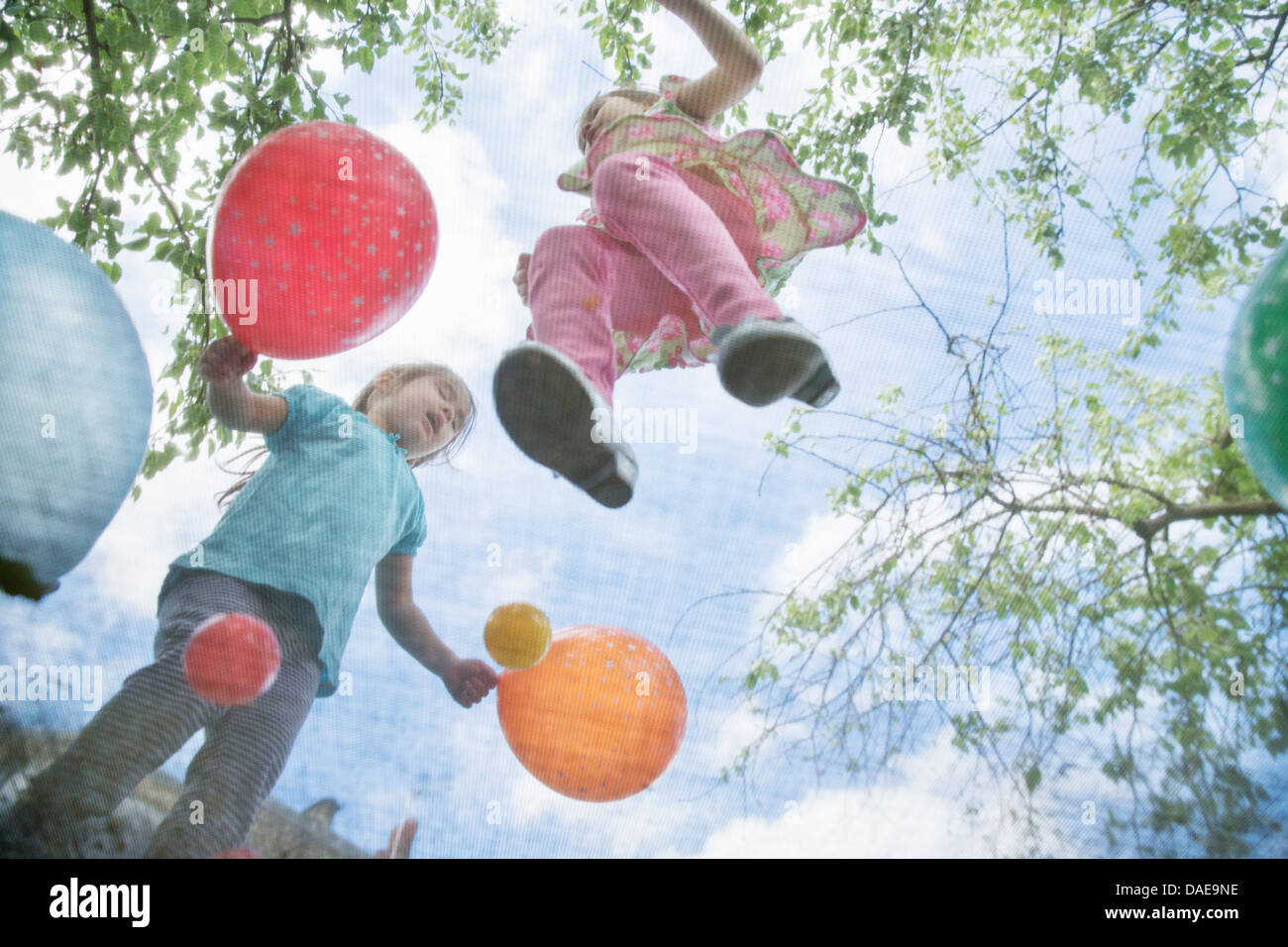 Young girls jumping on garden trampoline with balloons - Stock Image