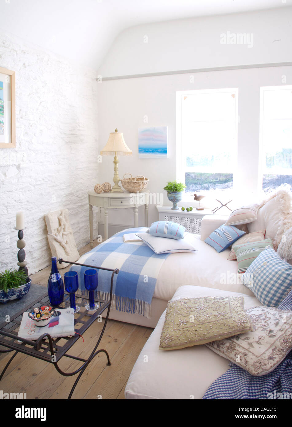 Cushions on white sofa in white coastal cottage living room with ...