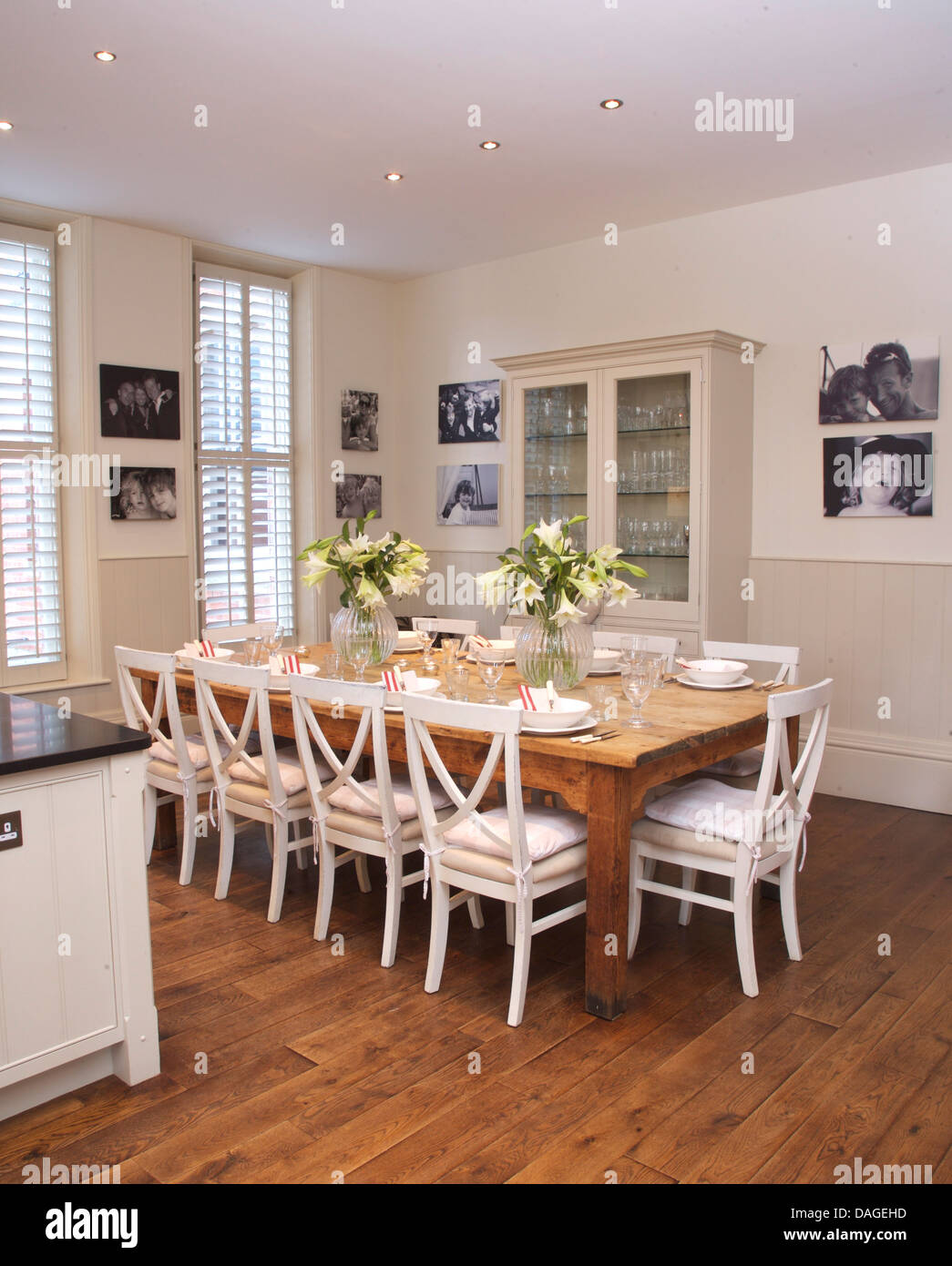White Chairs At Simple Wood Table In Modern Kitchen Dining Room With Wooden Flooring And Framed Black Photographs