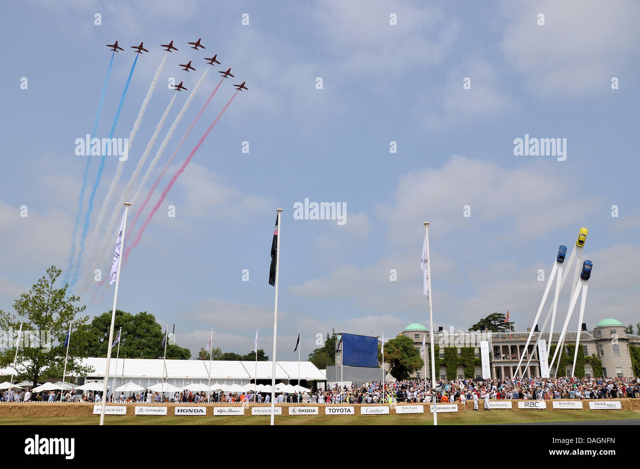 Red Arrows flypast over Goodwood House. The Goodwood Festival of Speed. Crowd. People. Porsche sculpture. Space Stock Photo