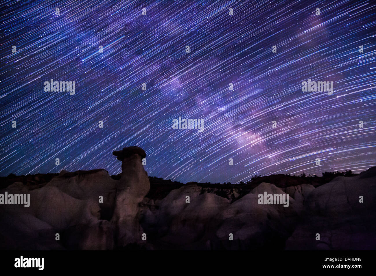 Star trails over unique rock formations in Colorado against the backdrop of a purple and pink Milky Way Galaxy Stock Photo