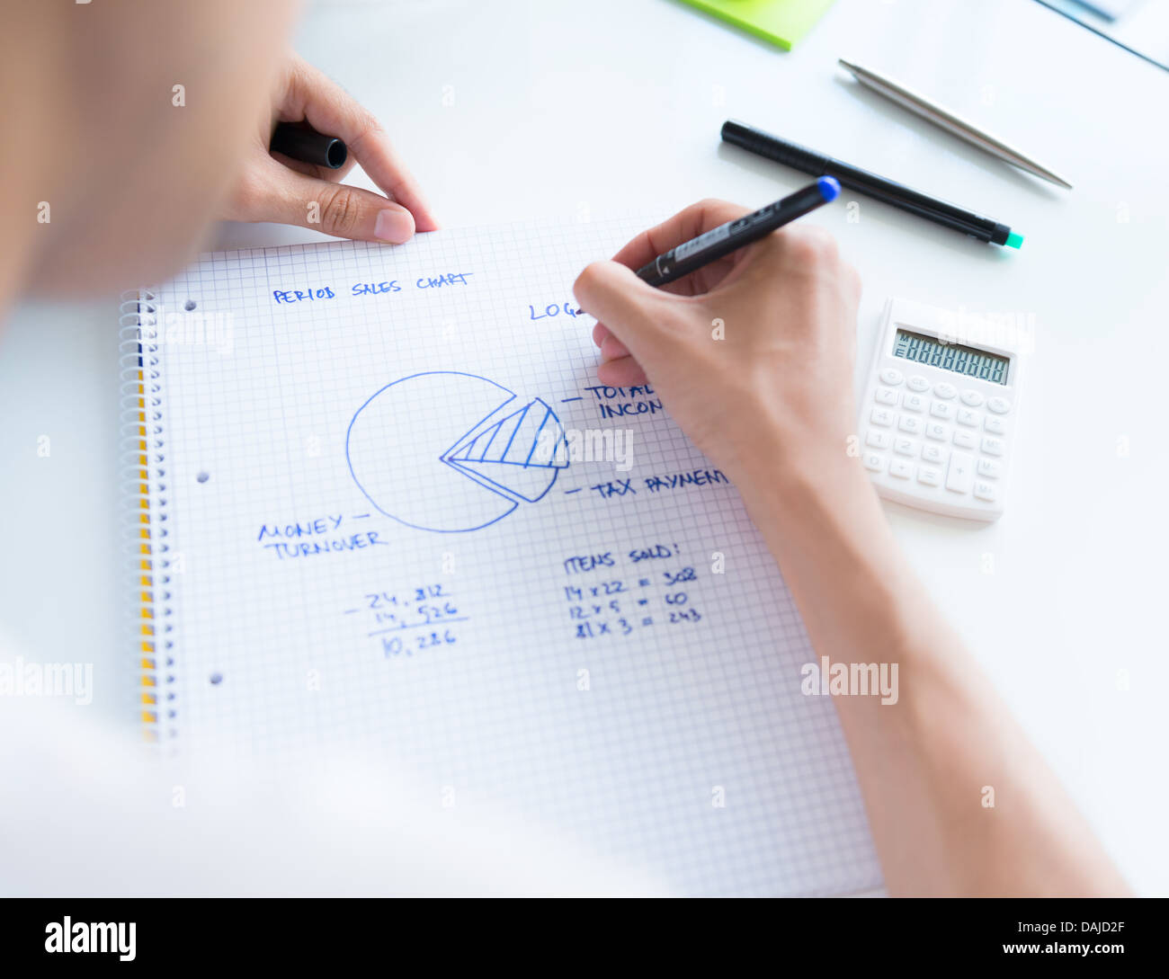 Person sitting at the desk, calculating sales earnings and drawing circular diagram with numbers - Stock Image