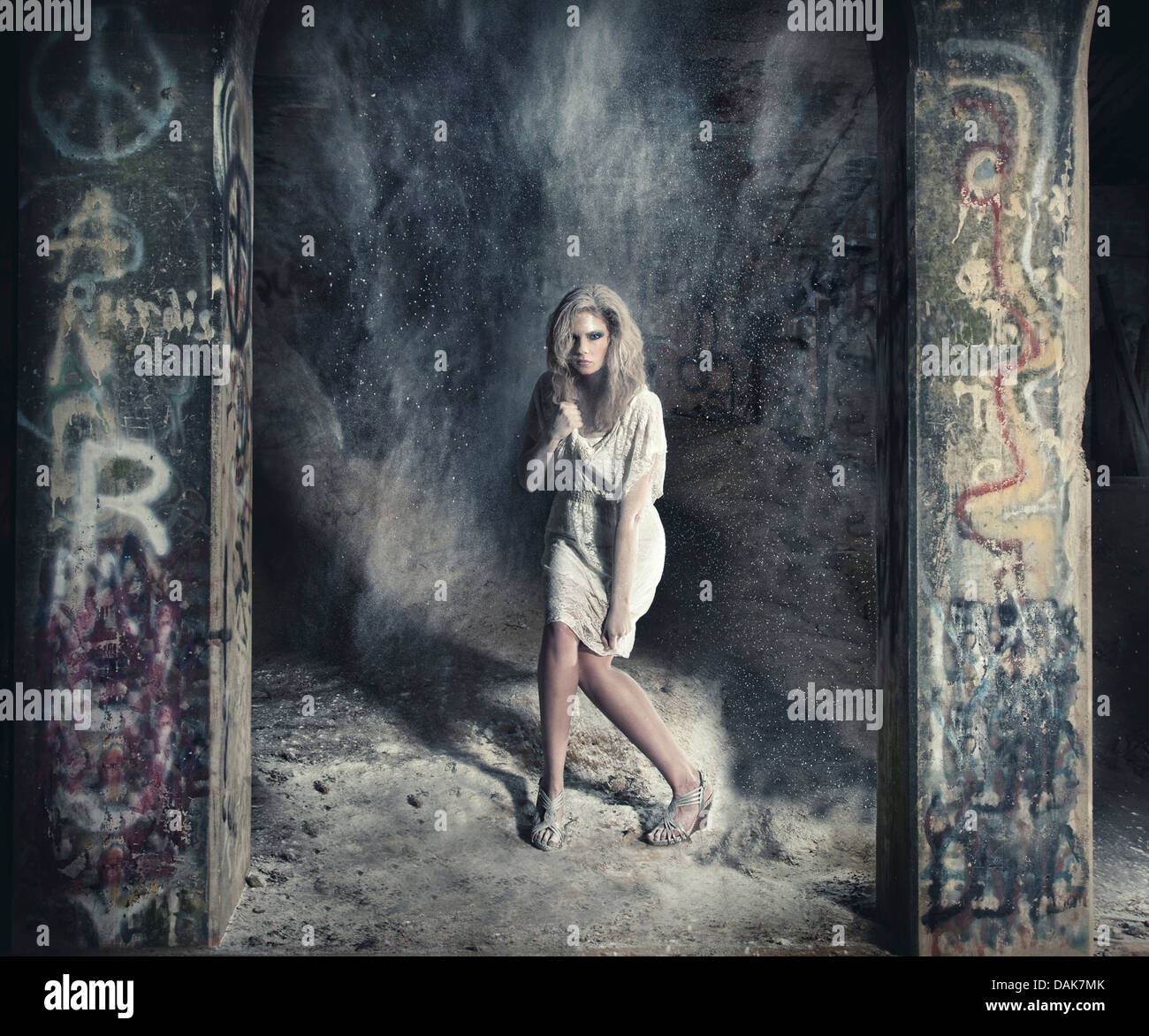Woman standing between two graffiti covered columns covered in dust - Stock Image