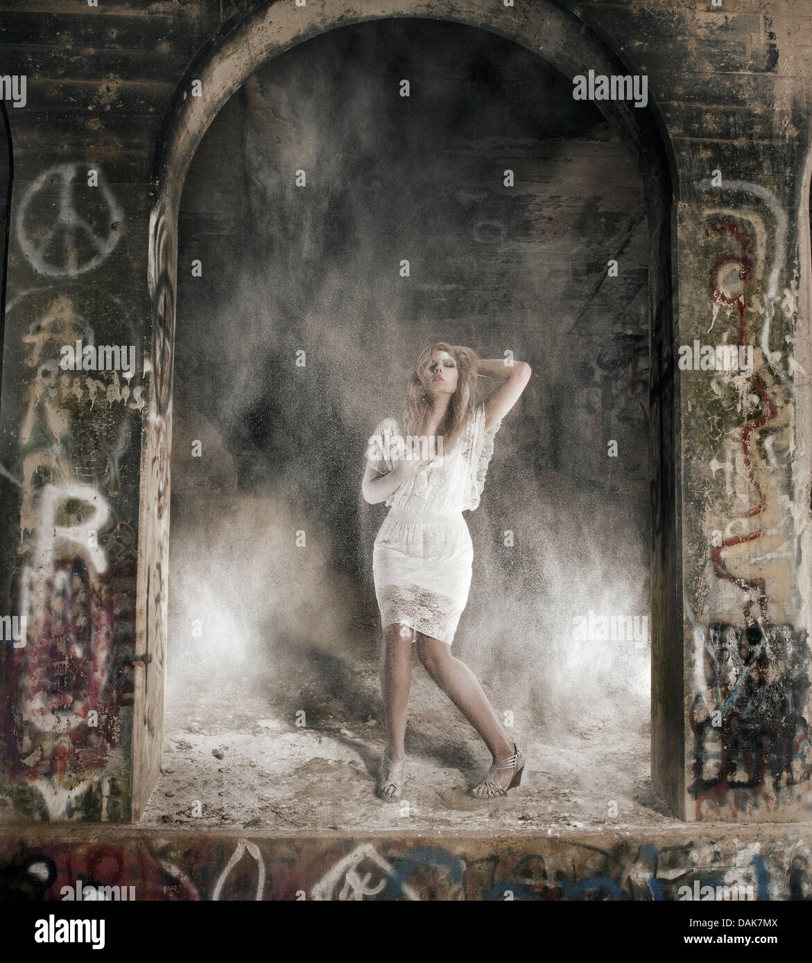 Woman between columns standing in dust cloud - Stock Image