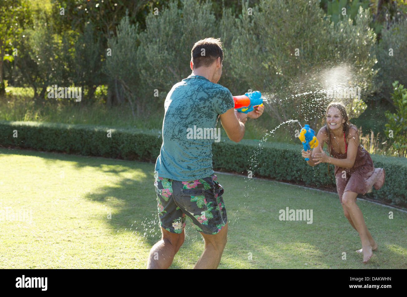 Couple playing with water guns in backyard - Stock Image