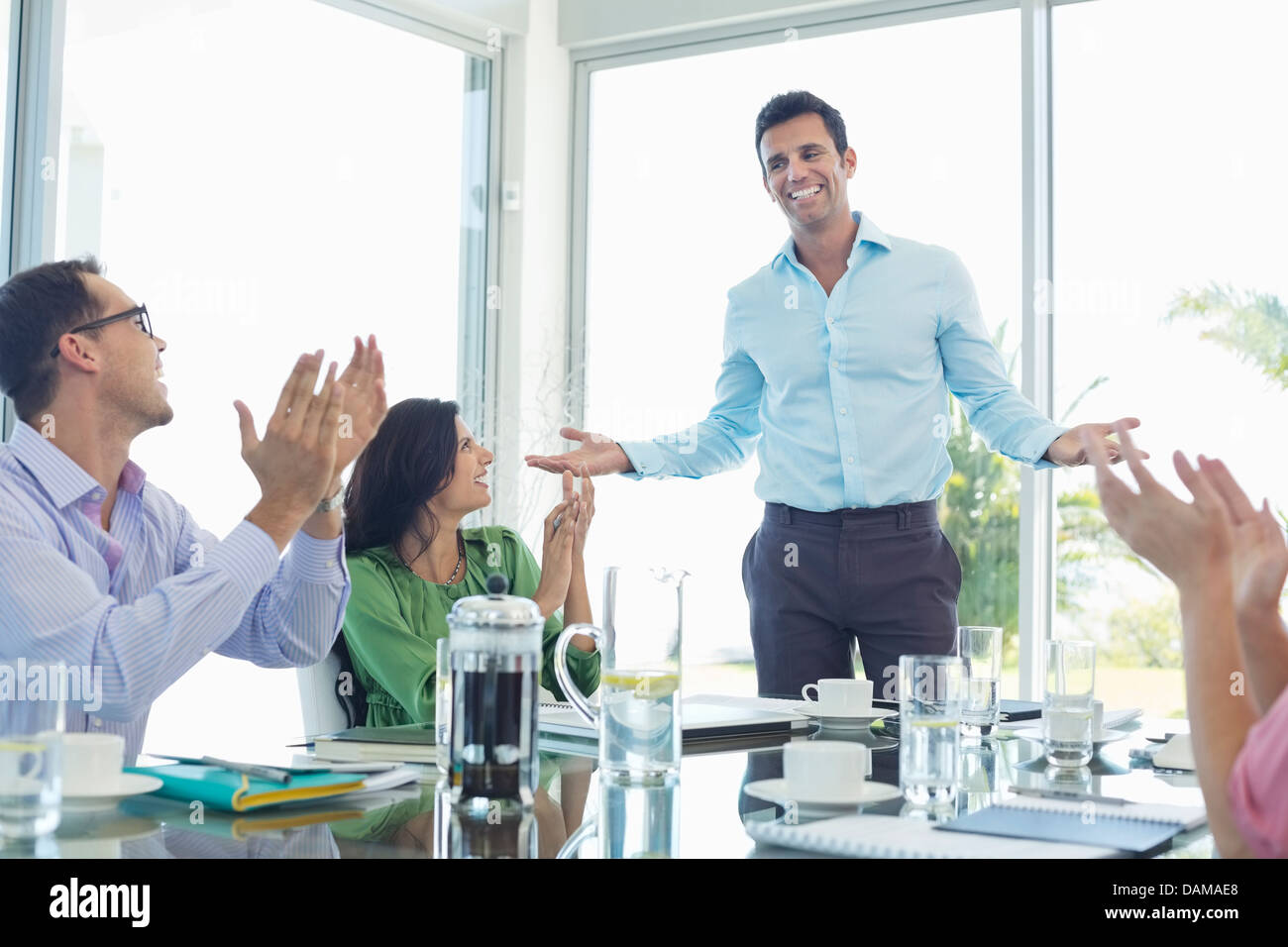 Business people cheering in meeting - Stock Image