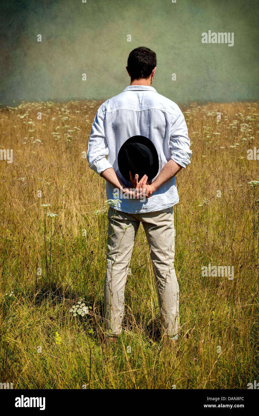 a man with a black hat standing on a field - Stock Image