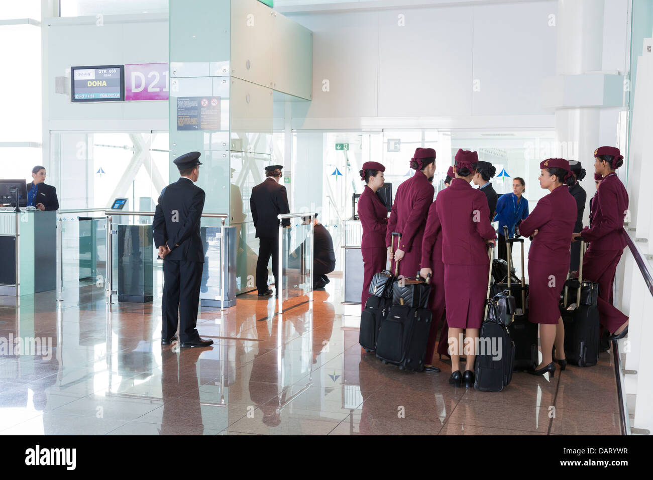 Qatar airways pilots and cabin staff waiting at airport departure gate. - Stock Image