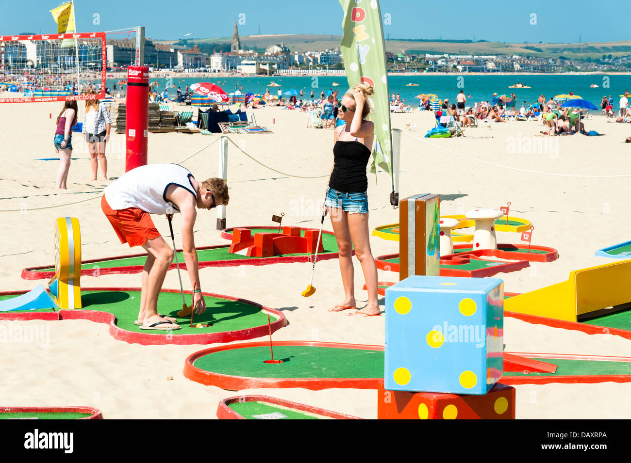 Young couple playing a game of crazy golf on the beach at Weymouth Bay, Dorset, UK. - Stock Image