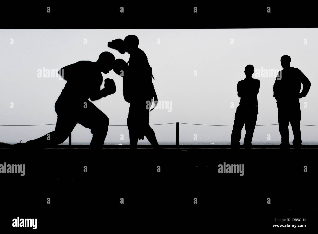 US Navy sailors practice boxing in the hangar bay aboard the aircraft carrier USS Nimitz silhouetted by a hazy sky - Stock Image