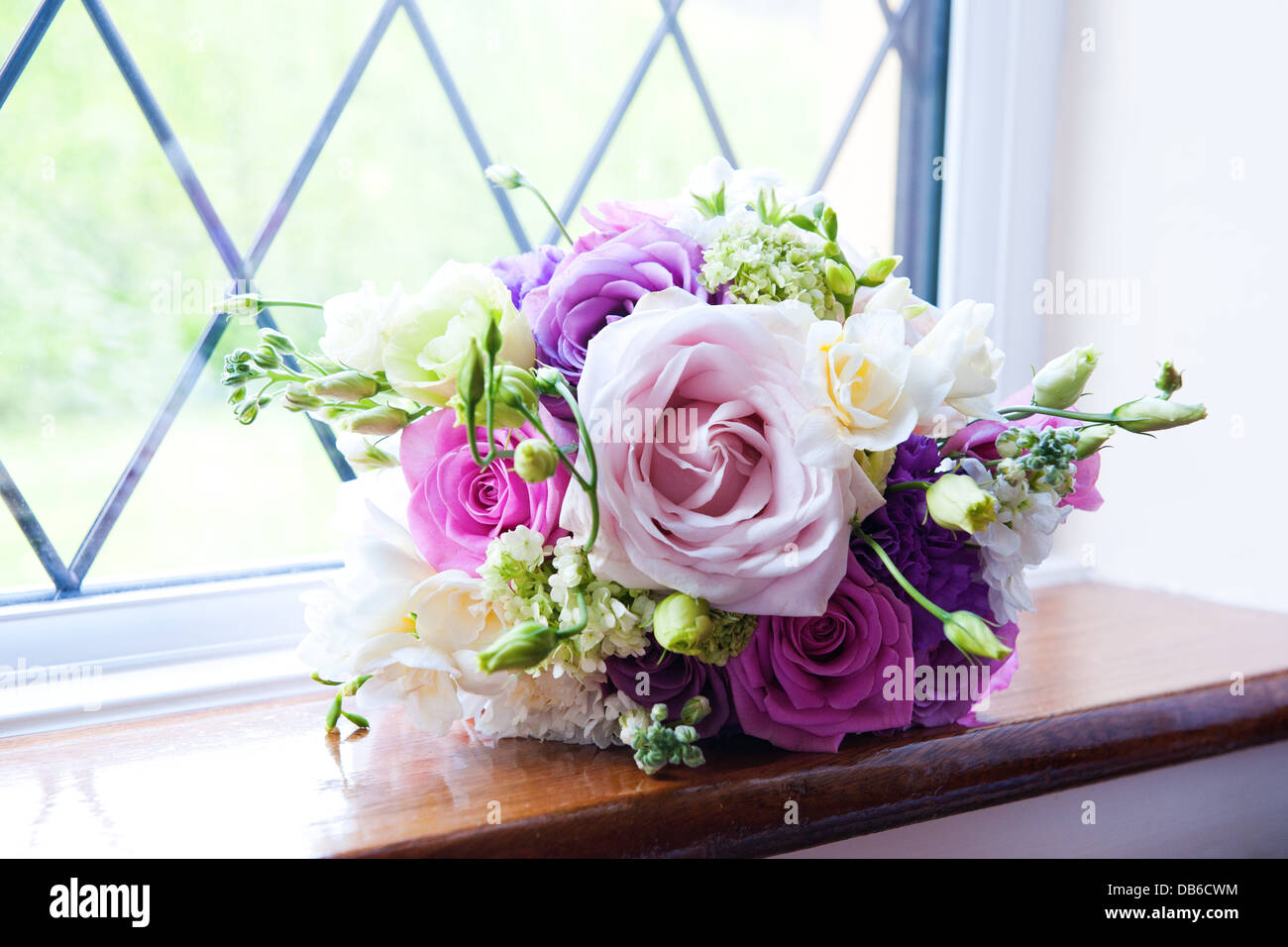 Vibrant purple pink white and pastel pink rose wedding flower vibrant purple pink white and pastel pink rose wedding flower bouquet on a wooden windowsill backlit izmirmasajfo Images