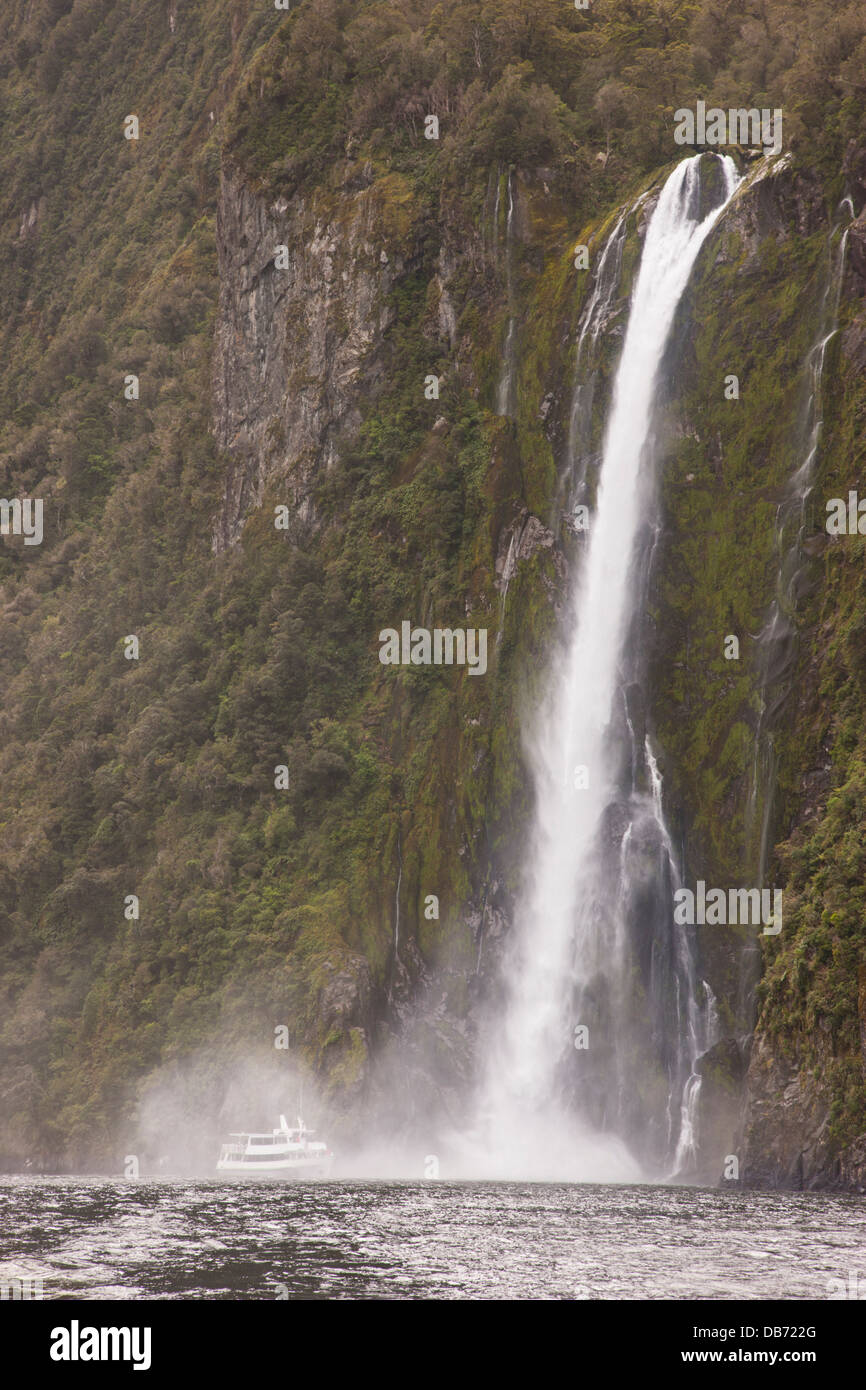 South Pacific, New Zealand, South Island, Fiordland National Park. A tourist boat moves close to Stirling Falls. - Stock Image