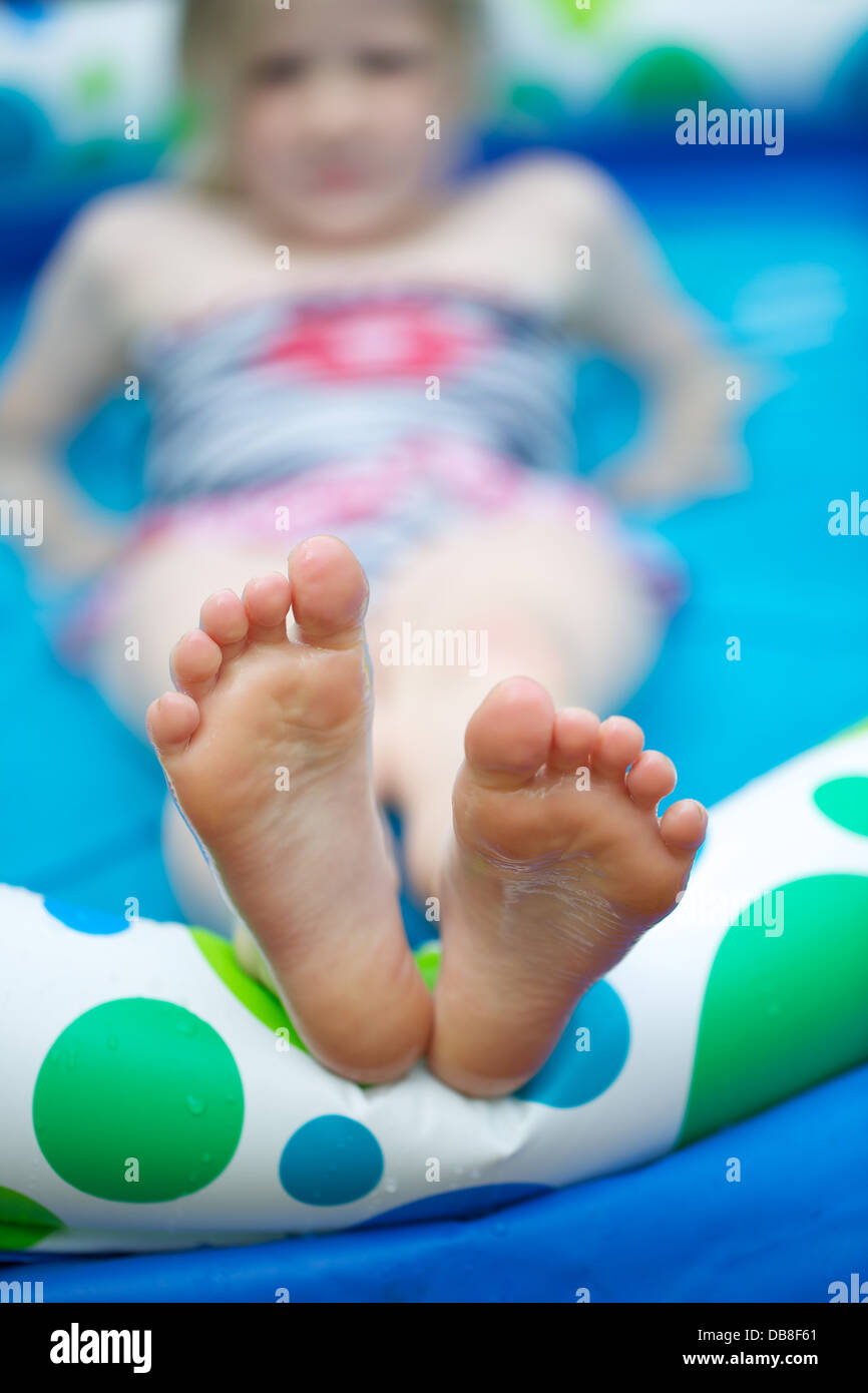 a young girl relaxing in a paddling pool in the summer sunshine with