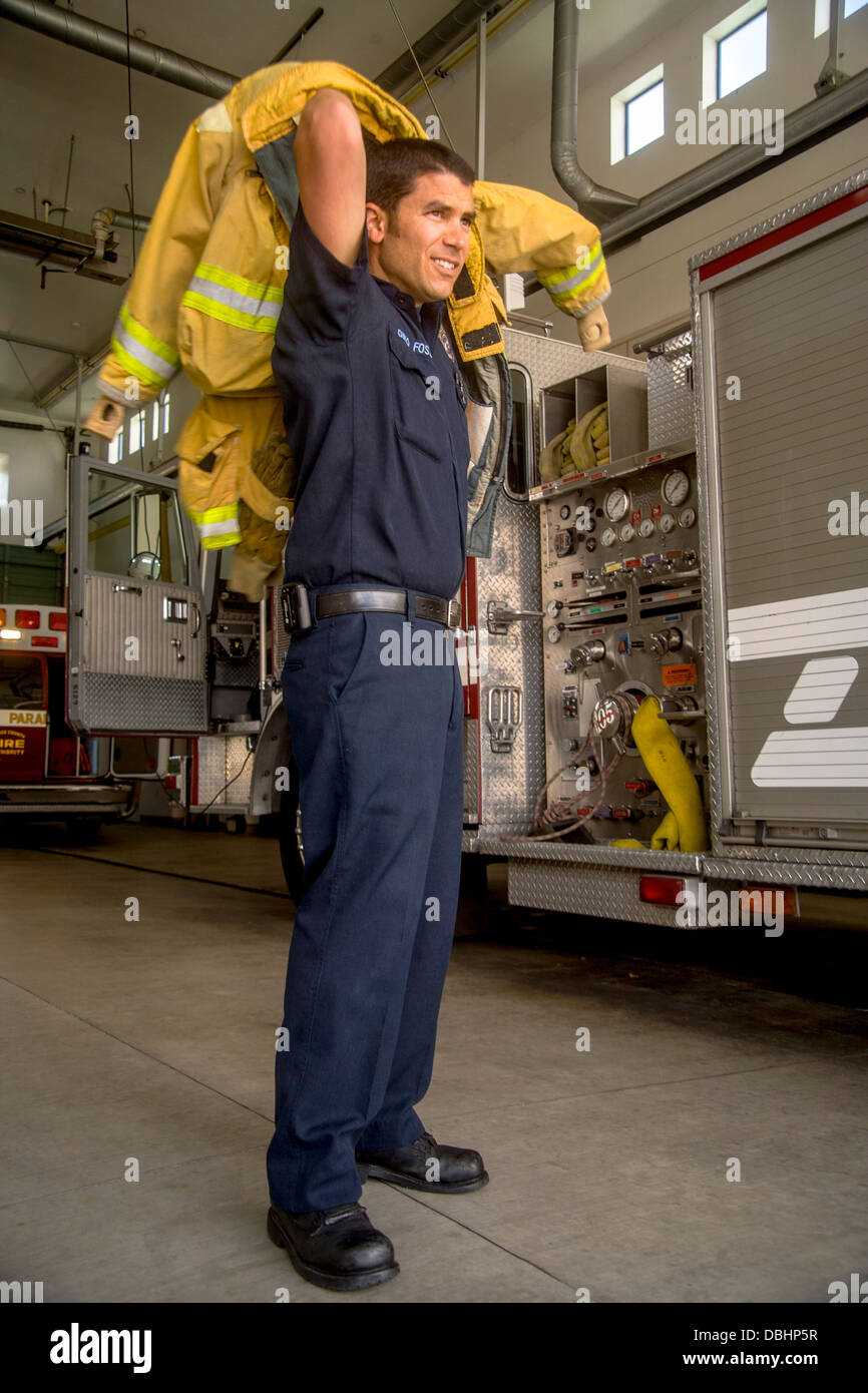 A young firefighter dons his yellow safety jacket at a firehouse in Laguna Niguel, CA. - Stock Image