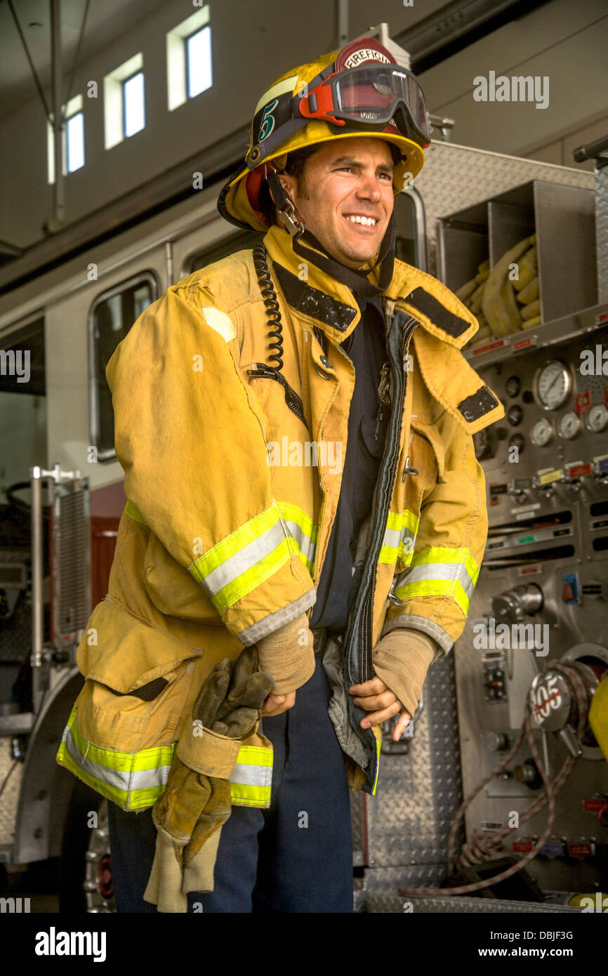 Wearing his helmet, a young firefighter dons his yellow safety jacket at a firehouse in Laguna Niguel, CA. - Stock Image