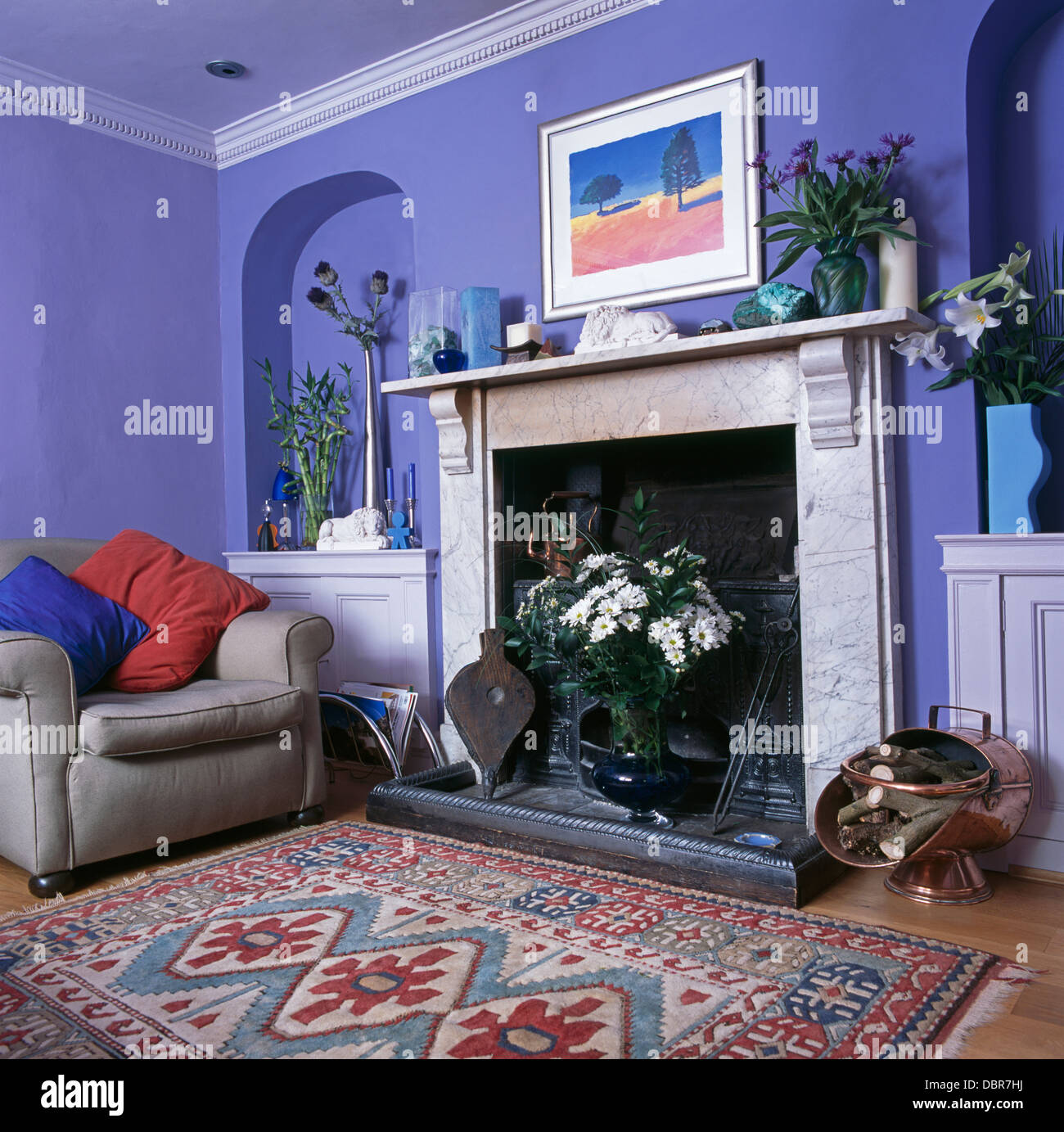Patterned Rug In Front Of Marble Fireplace In Blue Living Room With Gray  Armchair With Red And Blue Cushions In Front Of Alcove