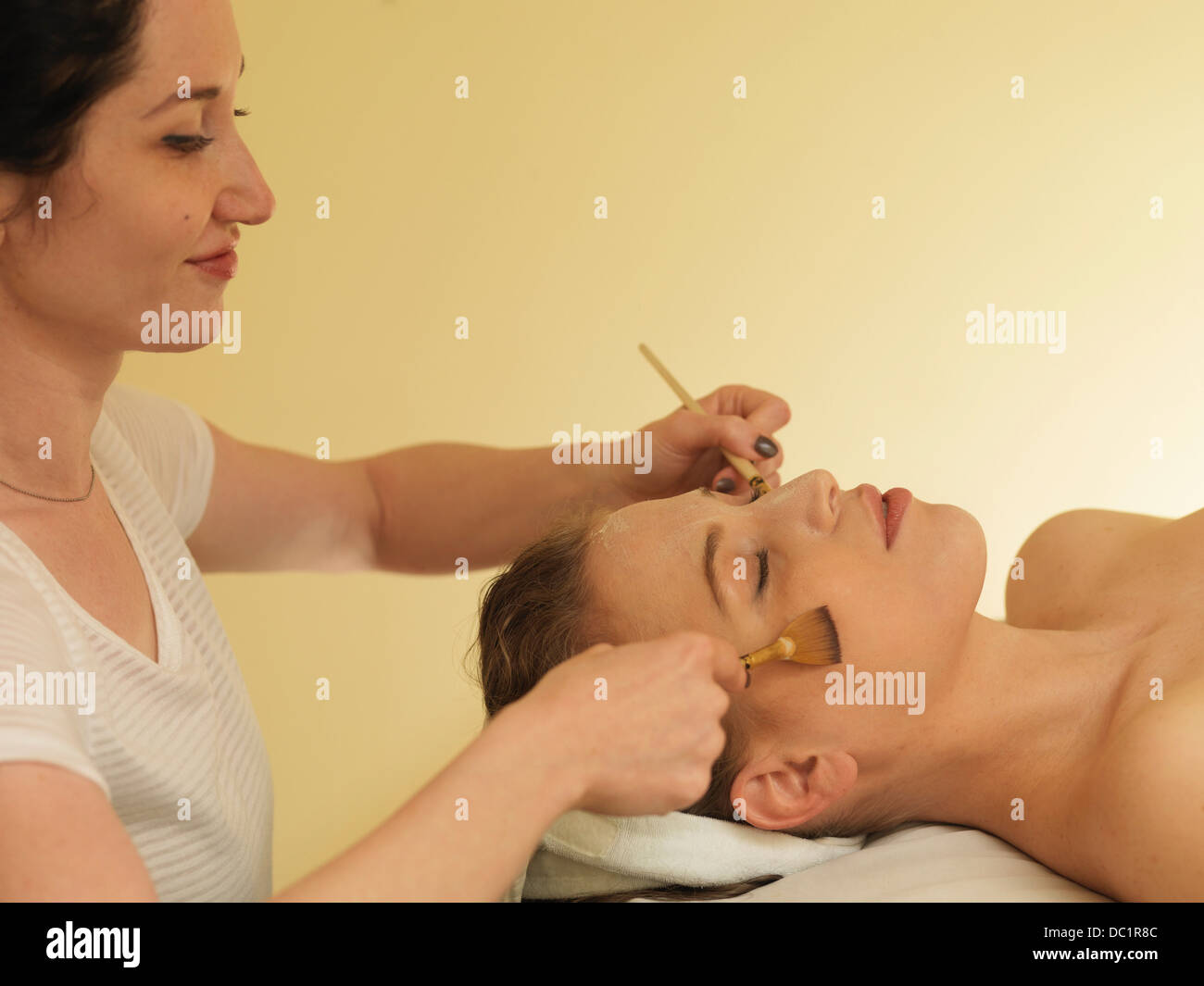 Young woman having face massage - Stock Image