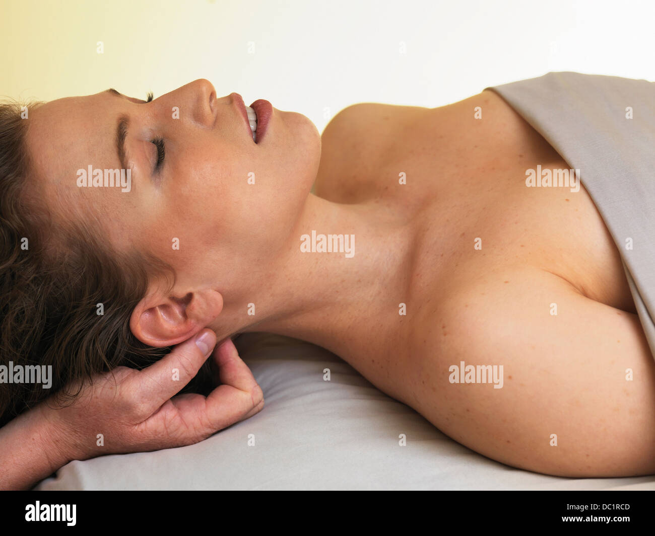 Young woman having her head massaged - Stock Image