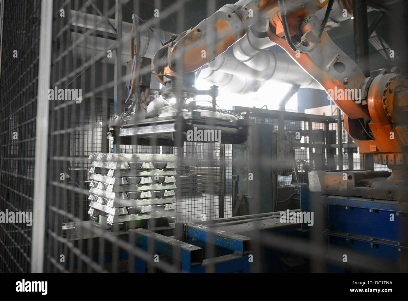 Heavy machinery lifting metal ingots at aluminum recycling plant - Stock Image