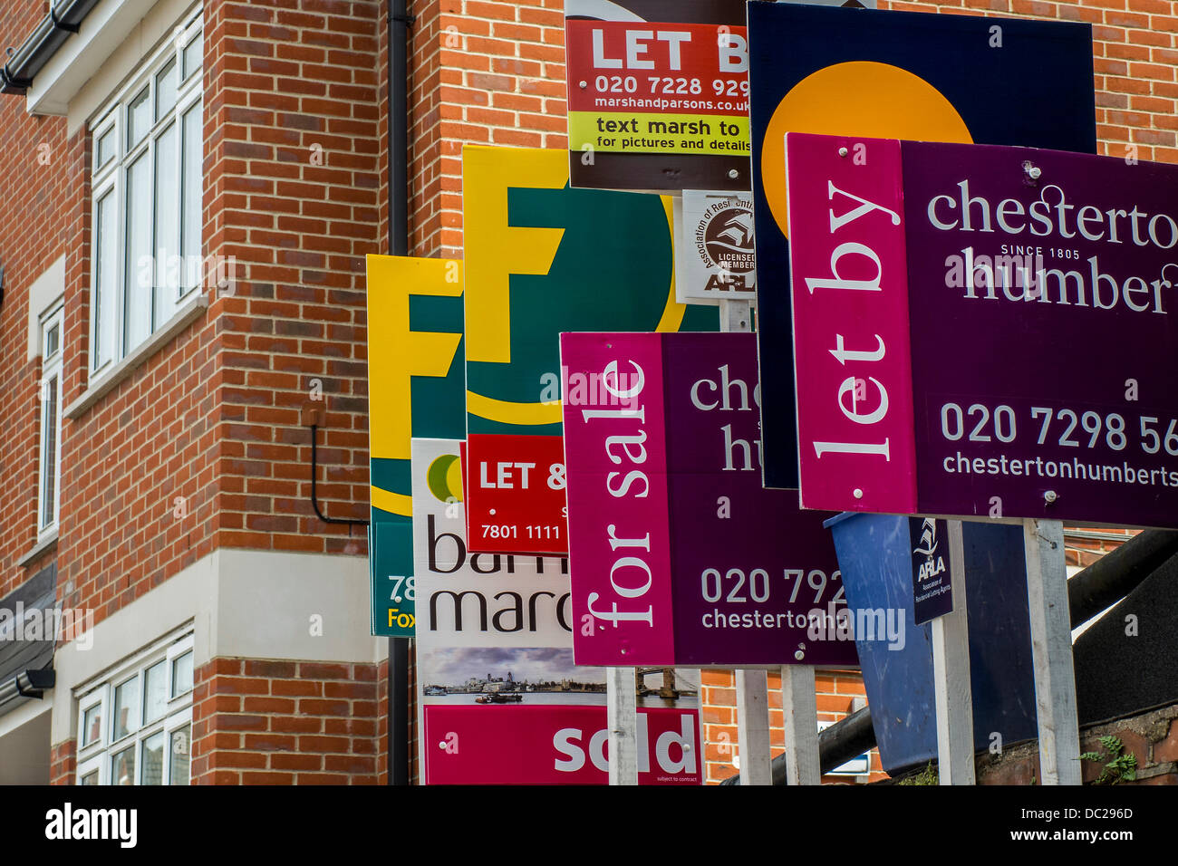 Competition in the housing market. A huge bunch of estate agents for sale and rental signs appear to be on one property Stock Photo