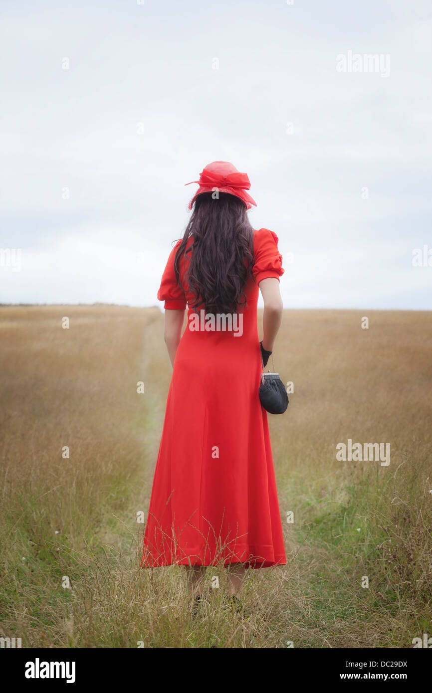 a woman in a red dress is walking over a field - Stock Image