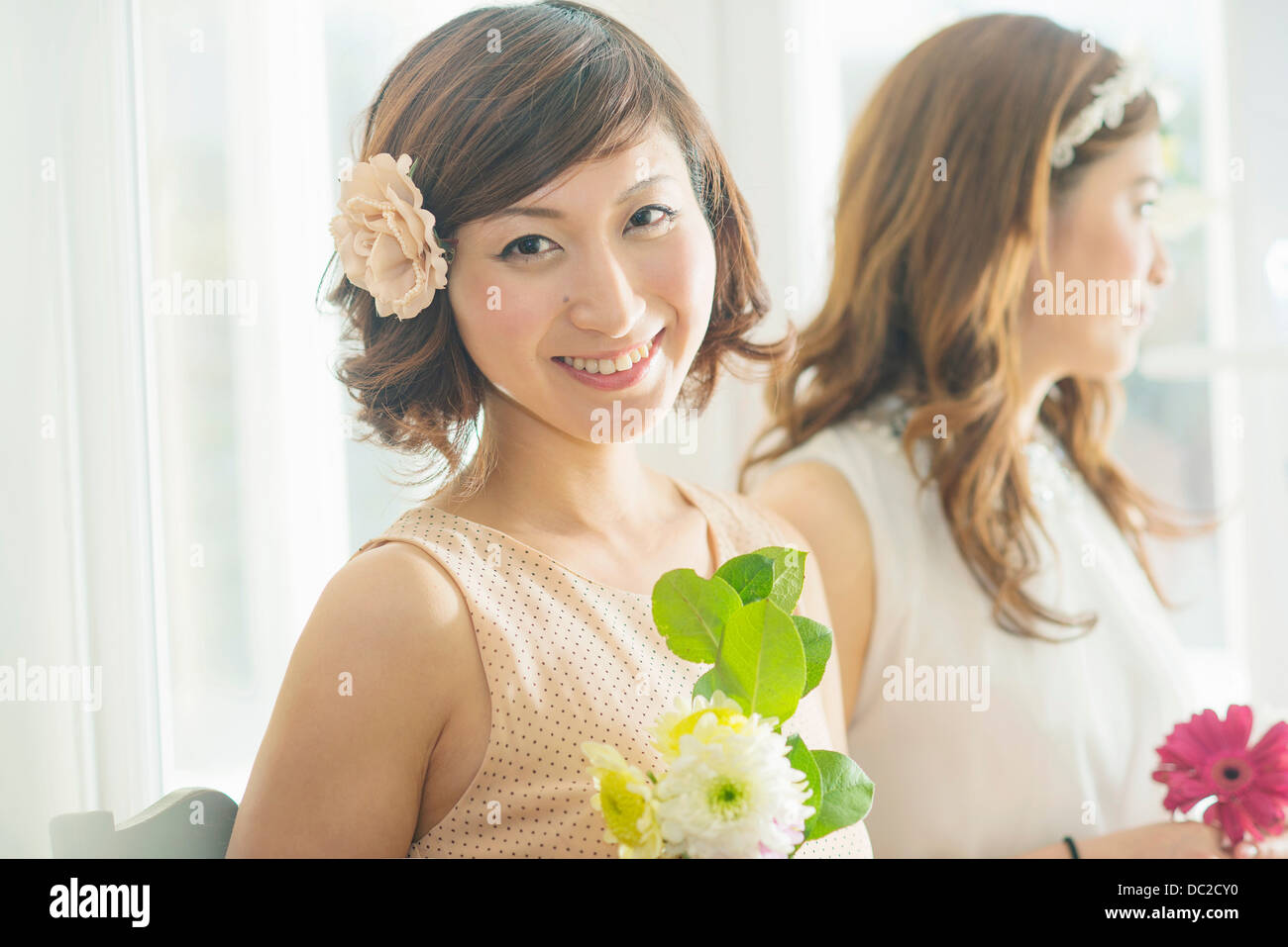 Smiling woman with flower looking at camera - Stock Image