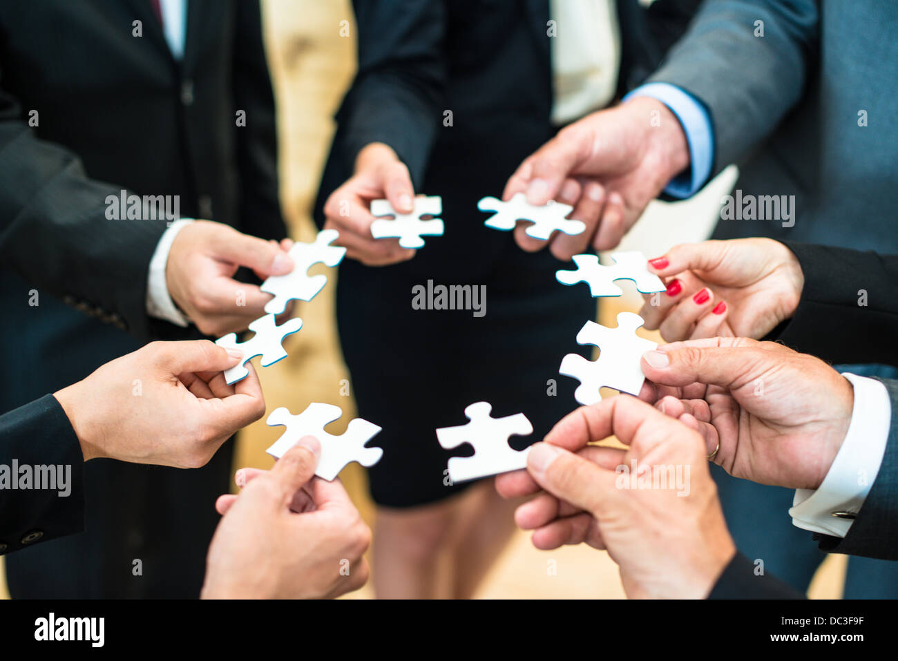 Teamwork - a group of eight business people assembling a jigsaw puzzle - representing team support and help concepts - Stock Image
