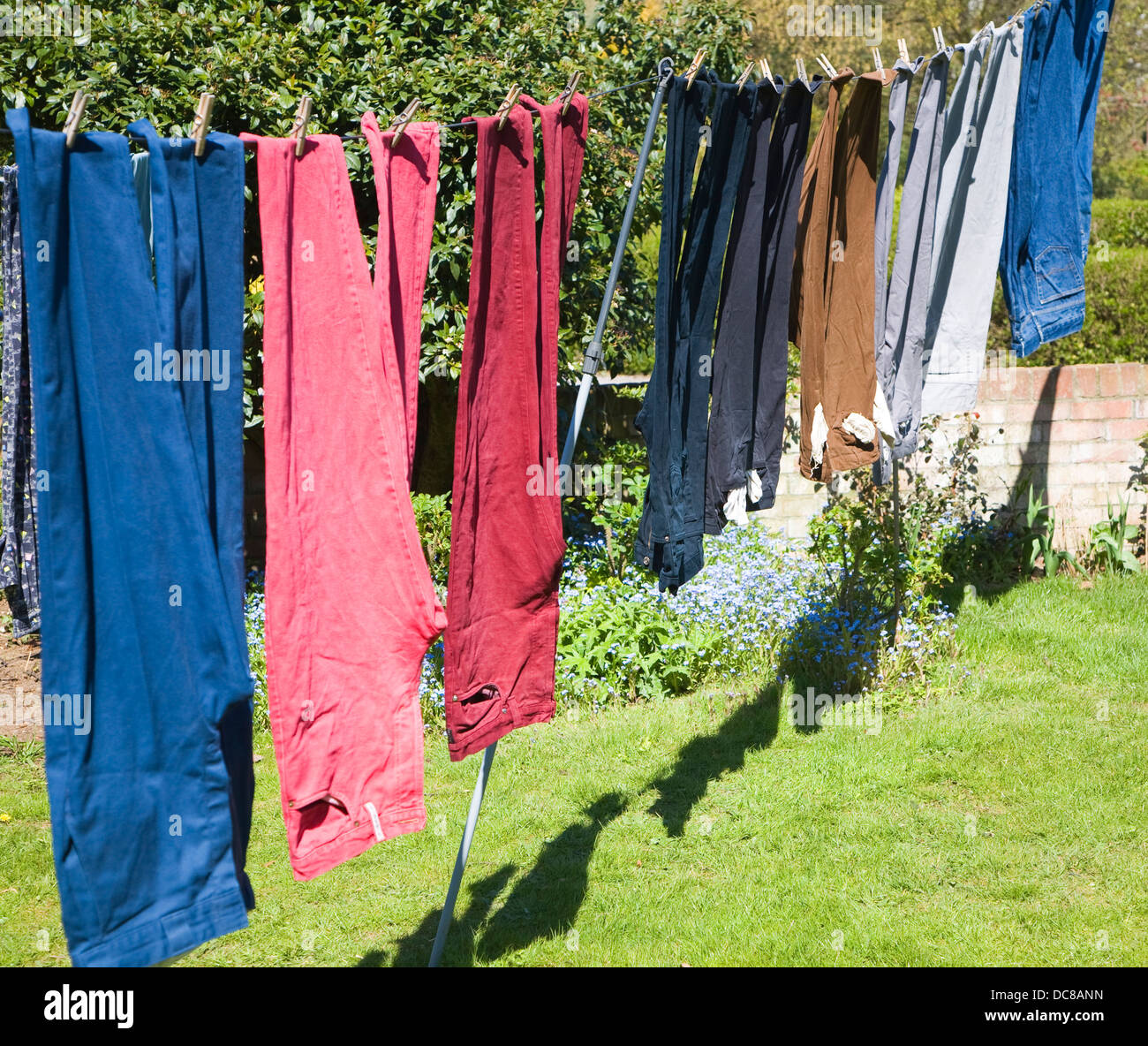 Washing line trousers drying in a garden on a sunny day - Stock Image
