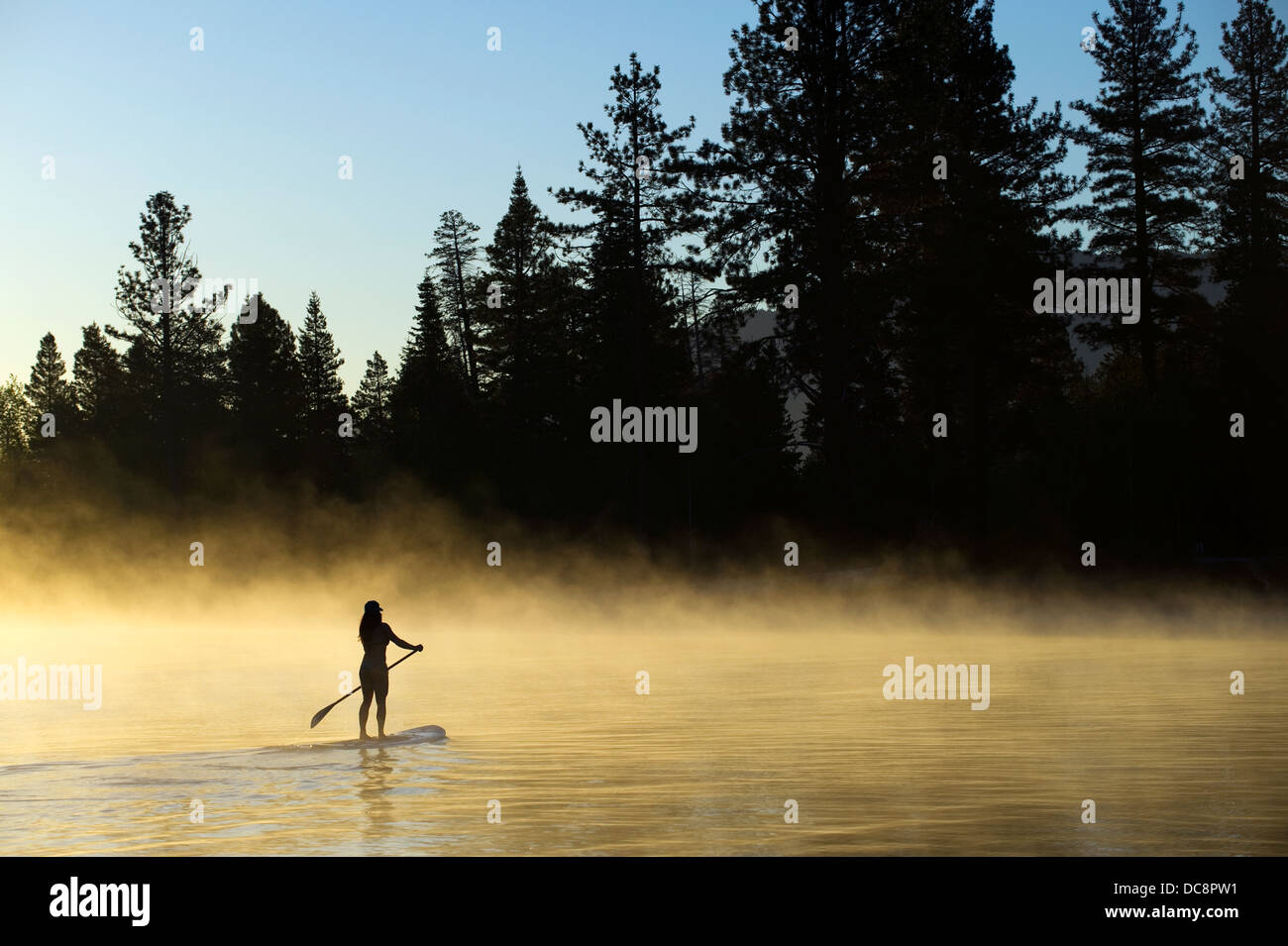 A woman, , is silhouetted Stand Up Paddleboarding (SUP) at sunrise in the mist in Lake Tahoe, CA. - Stock Image