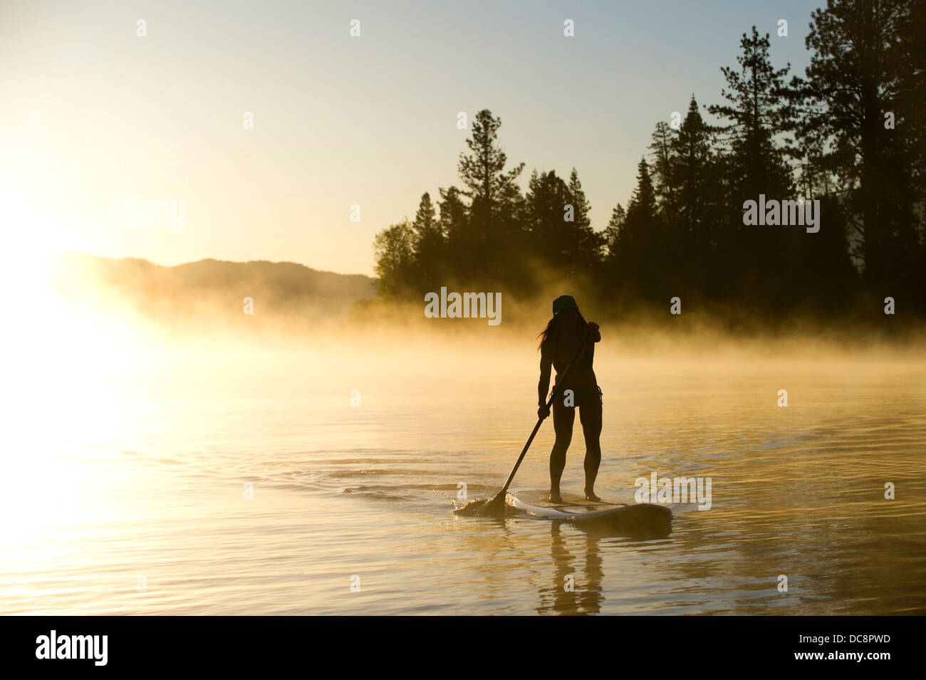 A woman, is silhouetted Stand Up Paddleboarding (SUP) at sunrise in the mist in Lake Tahoe, CA. - Stock Image