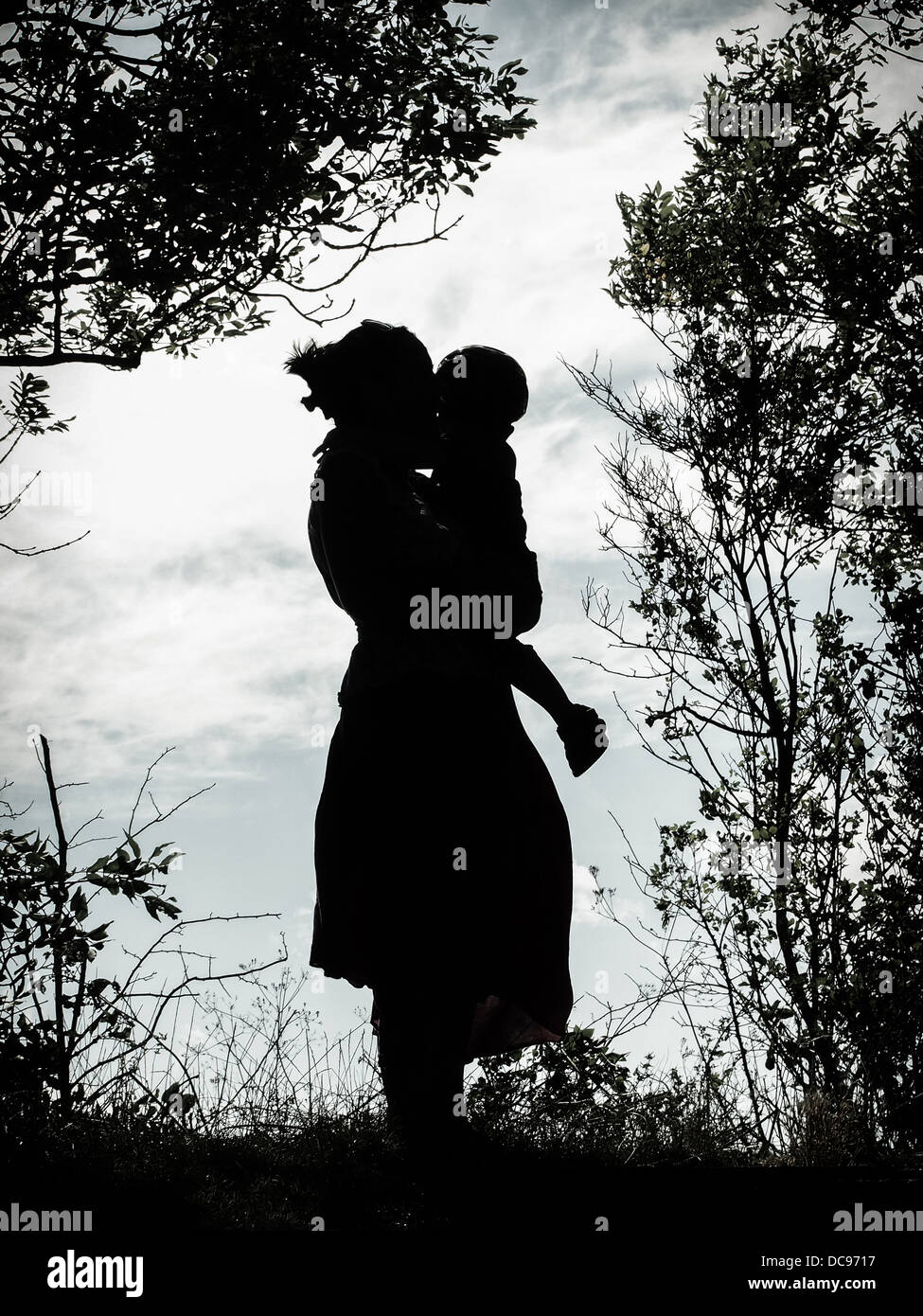 A silhouette of a mother holding a young boy wearing a cycle helmet framed by trees and branches Stock Photo