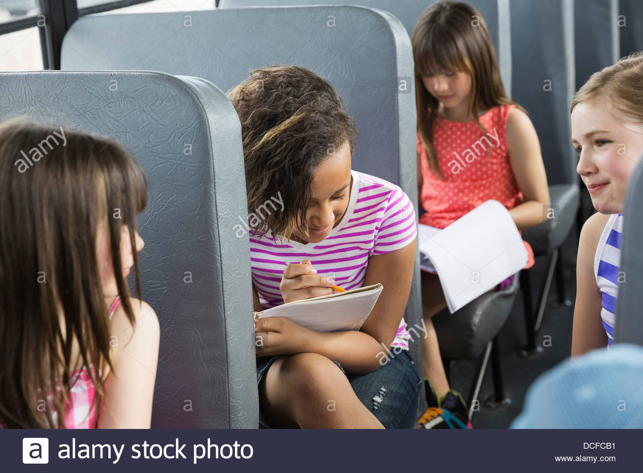 Schoolgirls sitting inside bus - Stock Image