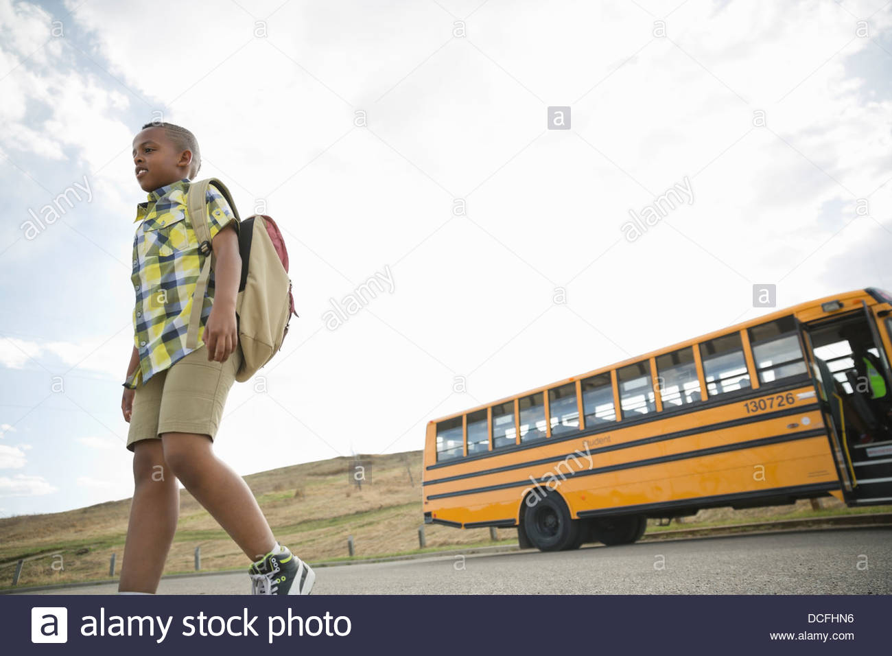 Low angle view of schoolboy walking away from school bus - Stock Image