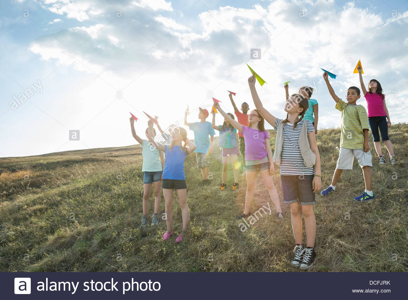 Group of kids gathered together holding paper airplanes - Stock Image